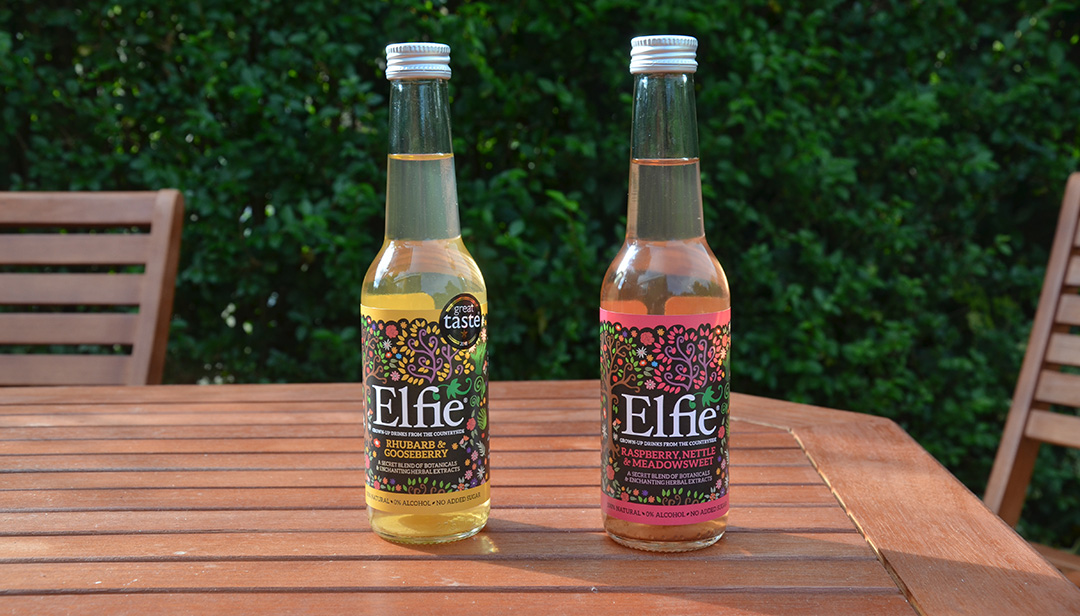 Grown-up drinks Elfie Drinks Pack shot on table by hedgerow